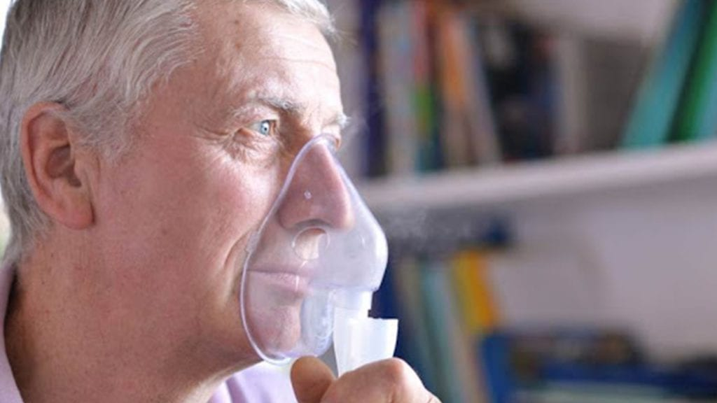Man with pulmonary fibrosis uses oxygen mask at home to protect himself from COVID-19