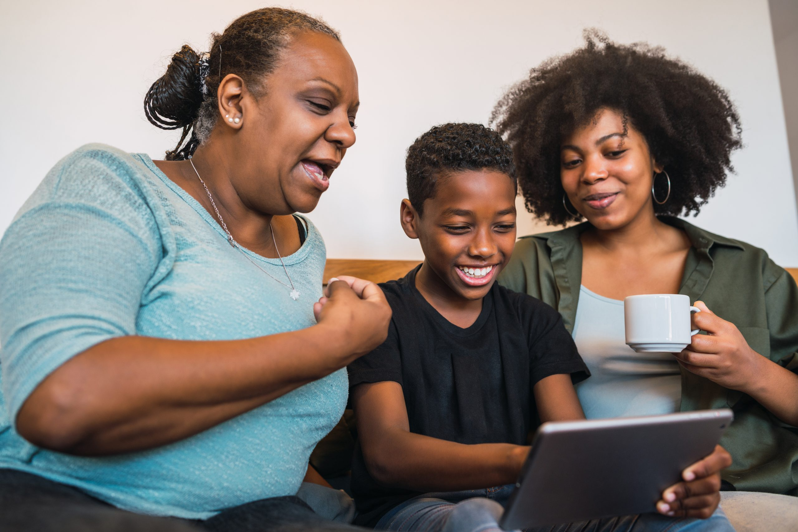 Black family on sofa looking at screen with grandmother at high risk for glaucoma