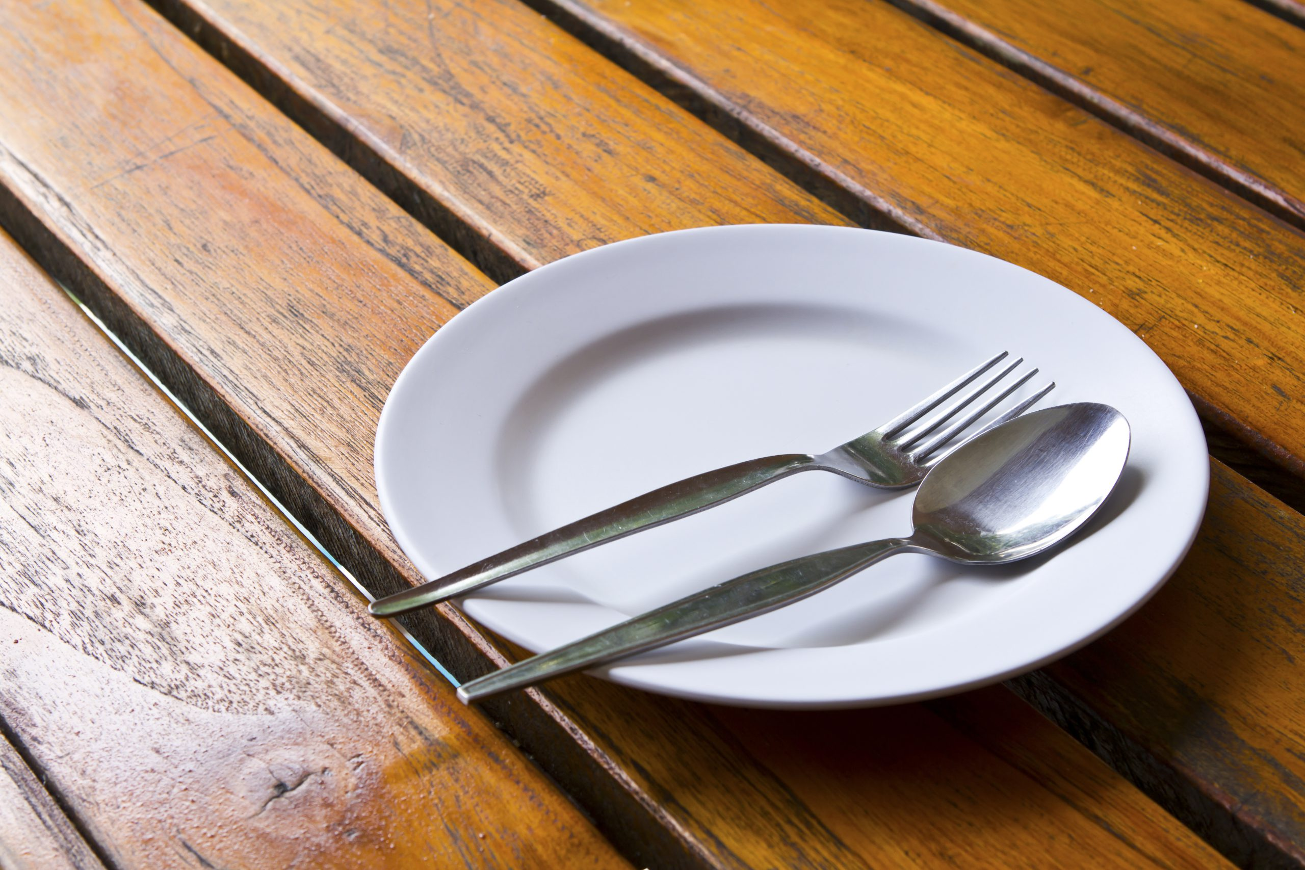 Empty plate with fork and spoon due to loss of appetite from kidney disease