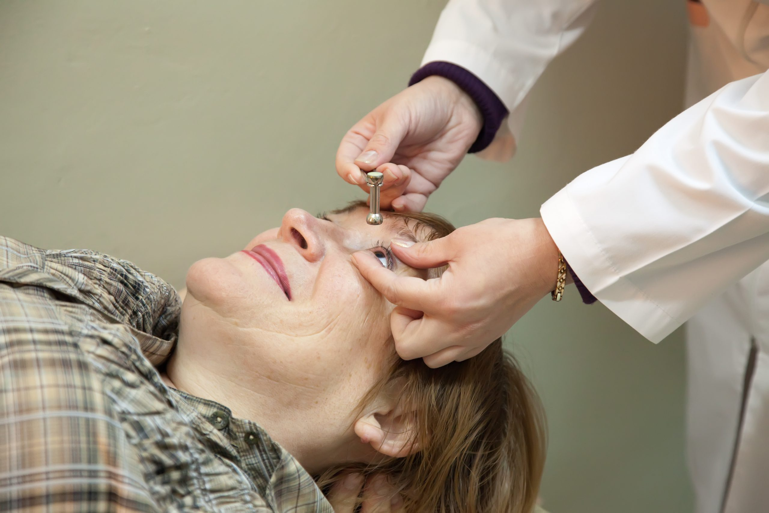 Ophthalmologist measures a patient's intraocular pressure (IOP) for glaucoma