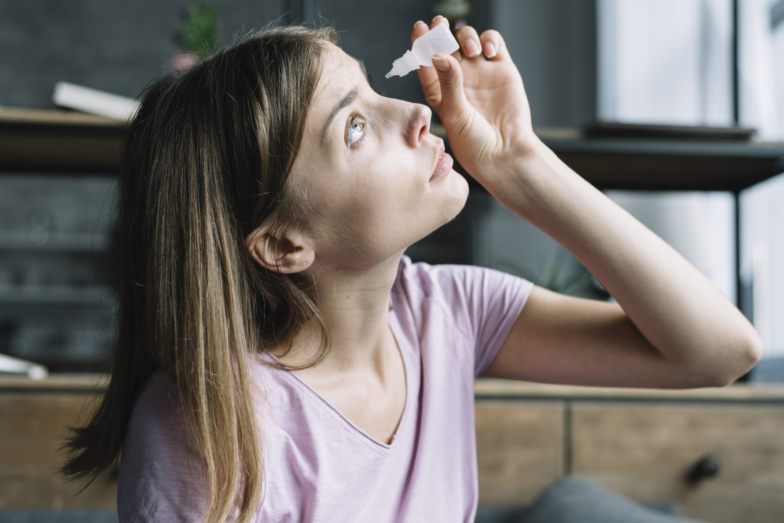 Young woman putting in eye drops for glaucoma treatment