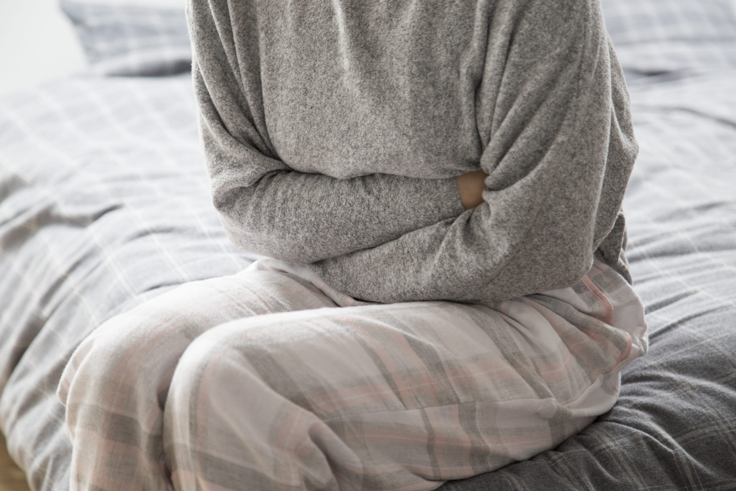 Woman in pajamas sitting on bed holding stomach in pain