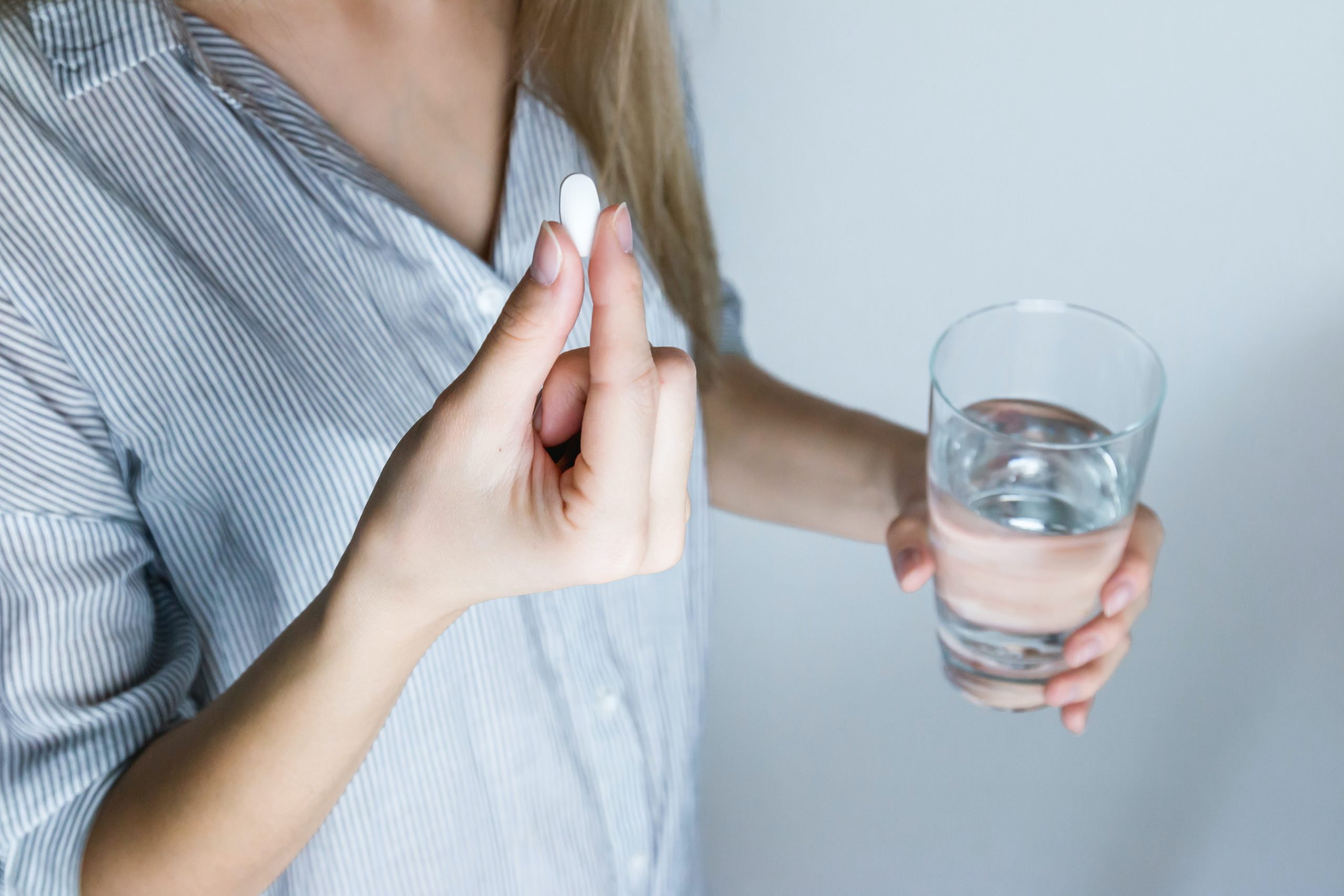 Woman with a pill in one hand and a glass of water in the other