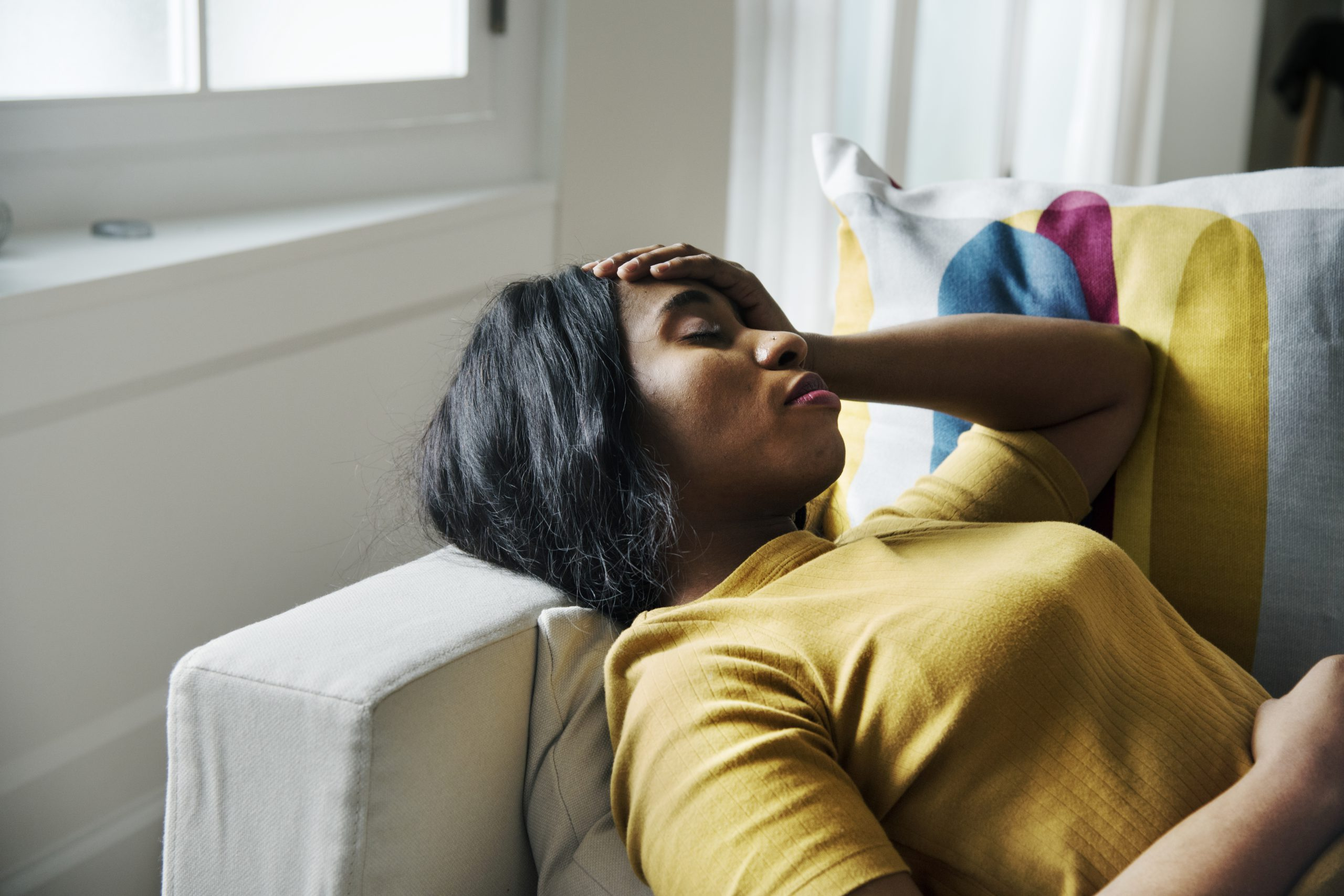 Black woman on sofa with hand on head worried about fibroids and asking for a second opinion