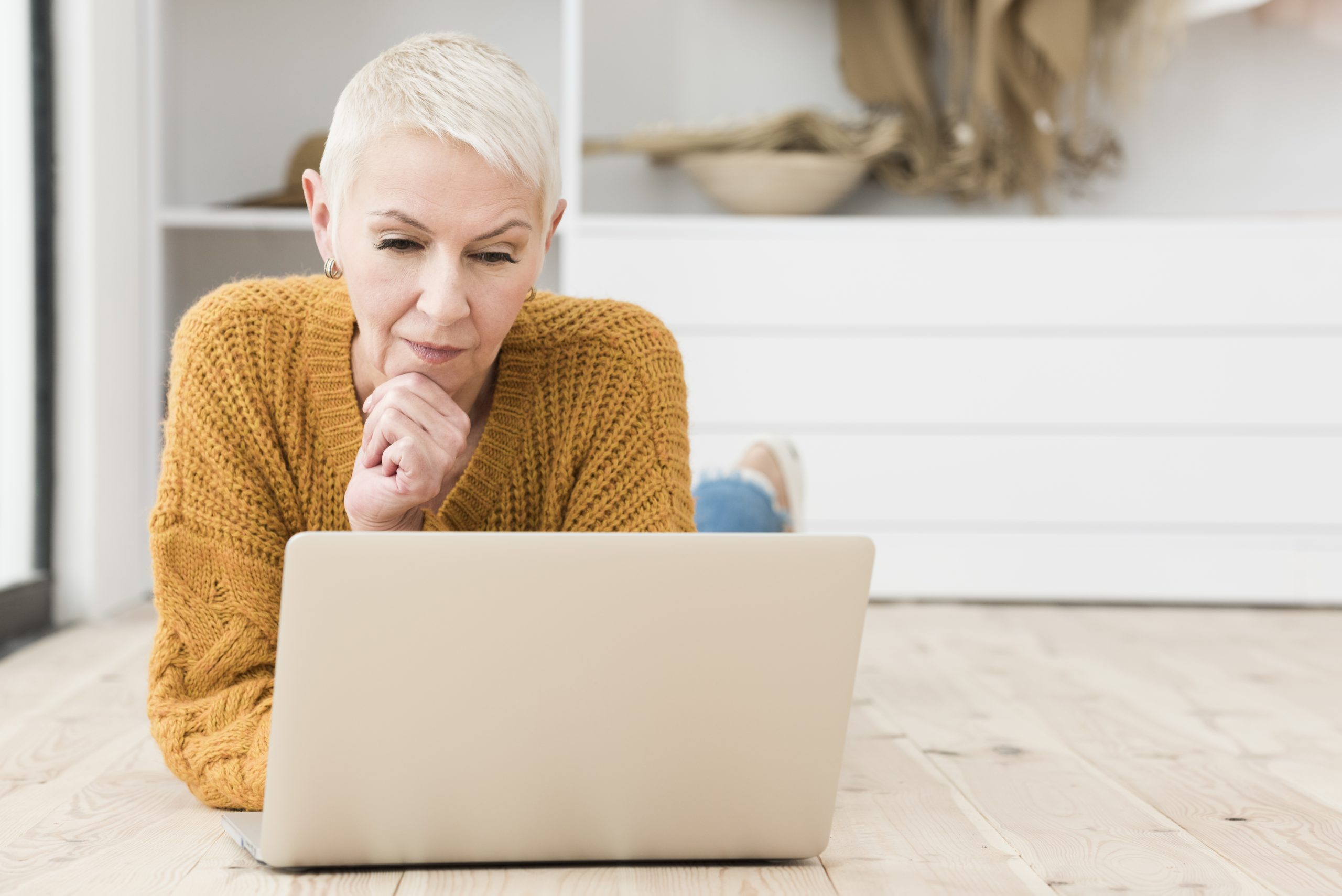 Older woman laying on floor looking at laptop considering second opinion on fibroids