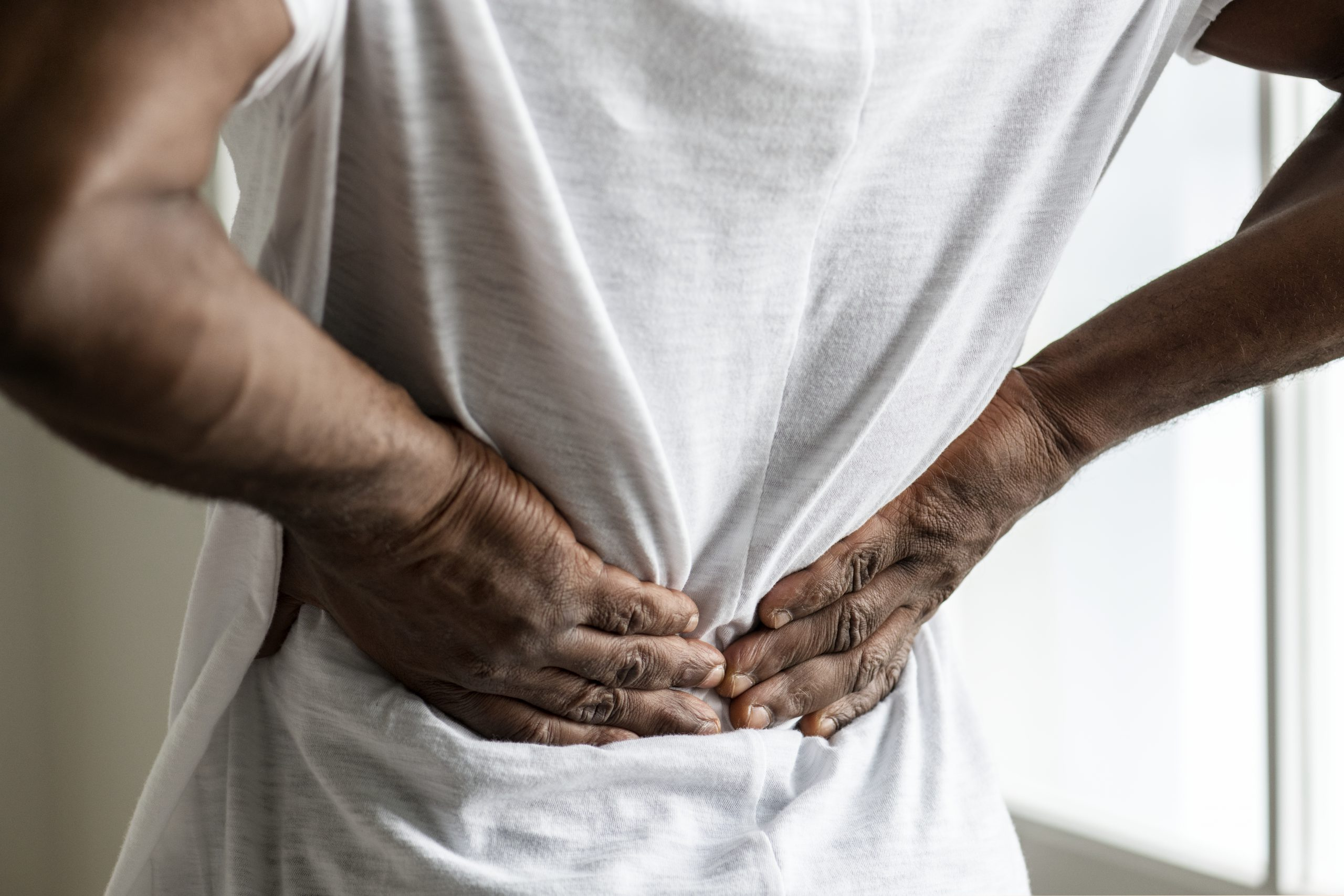 Black man from behind with hands on back in pain