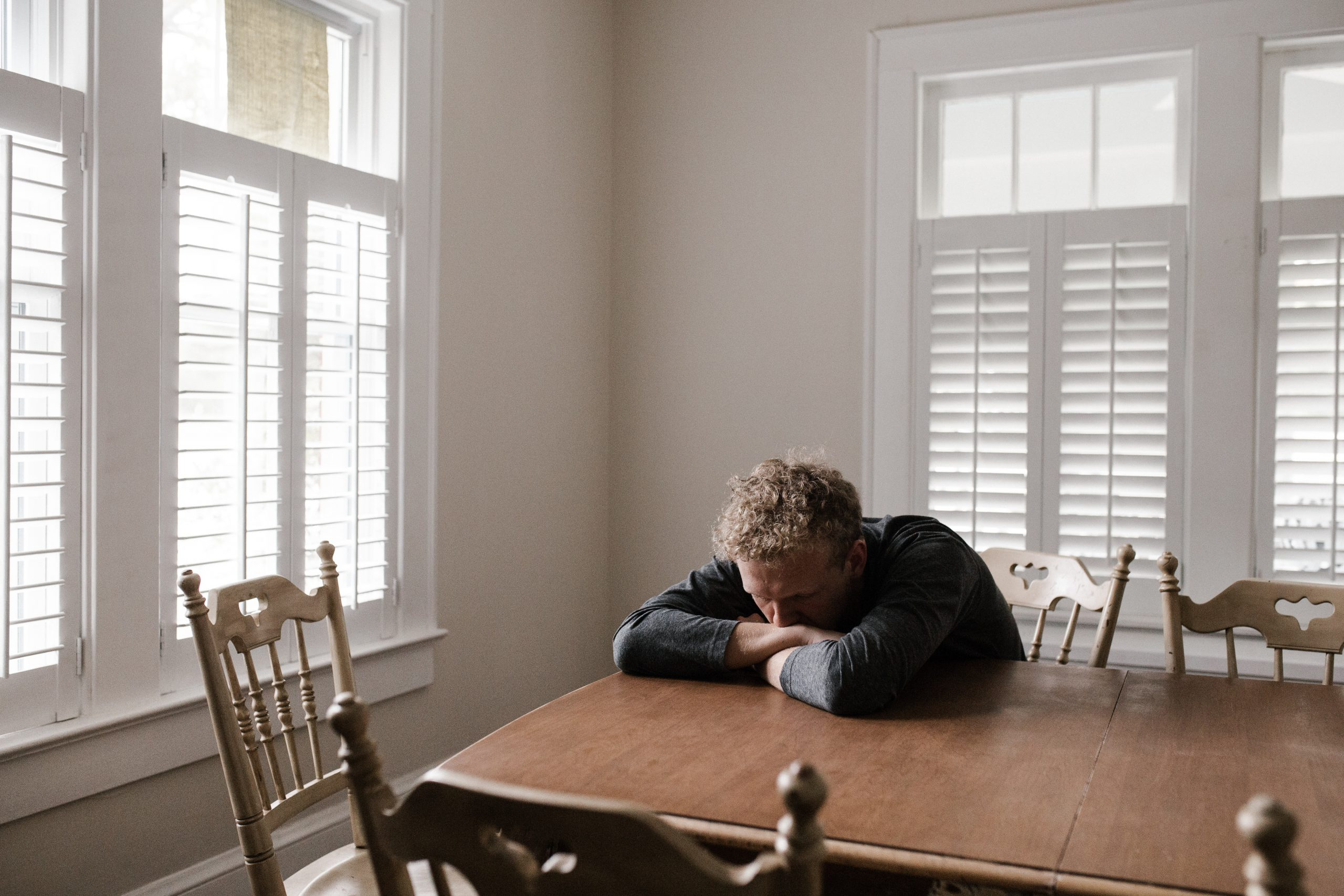 Man sitting down with head on table due to tiredness from stage 5 CKD