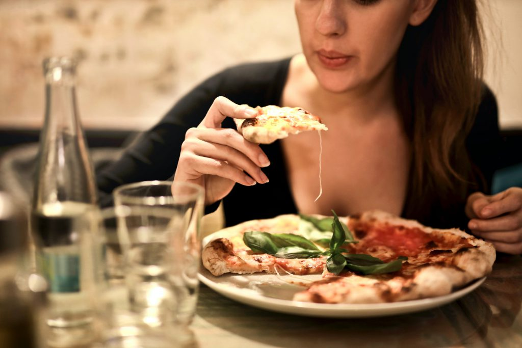 Woman eating pizza as a comfort food for fibroids symptoms