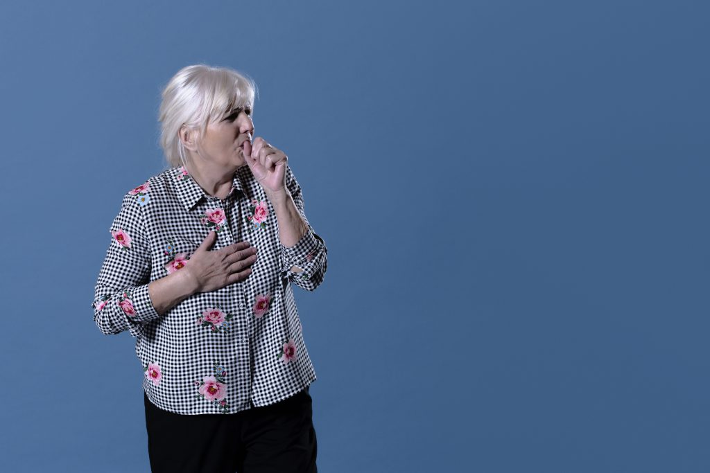 Older woman holding her chest and coughing