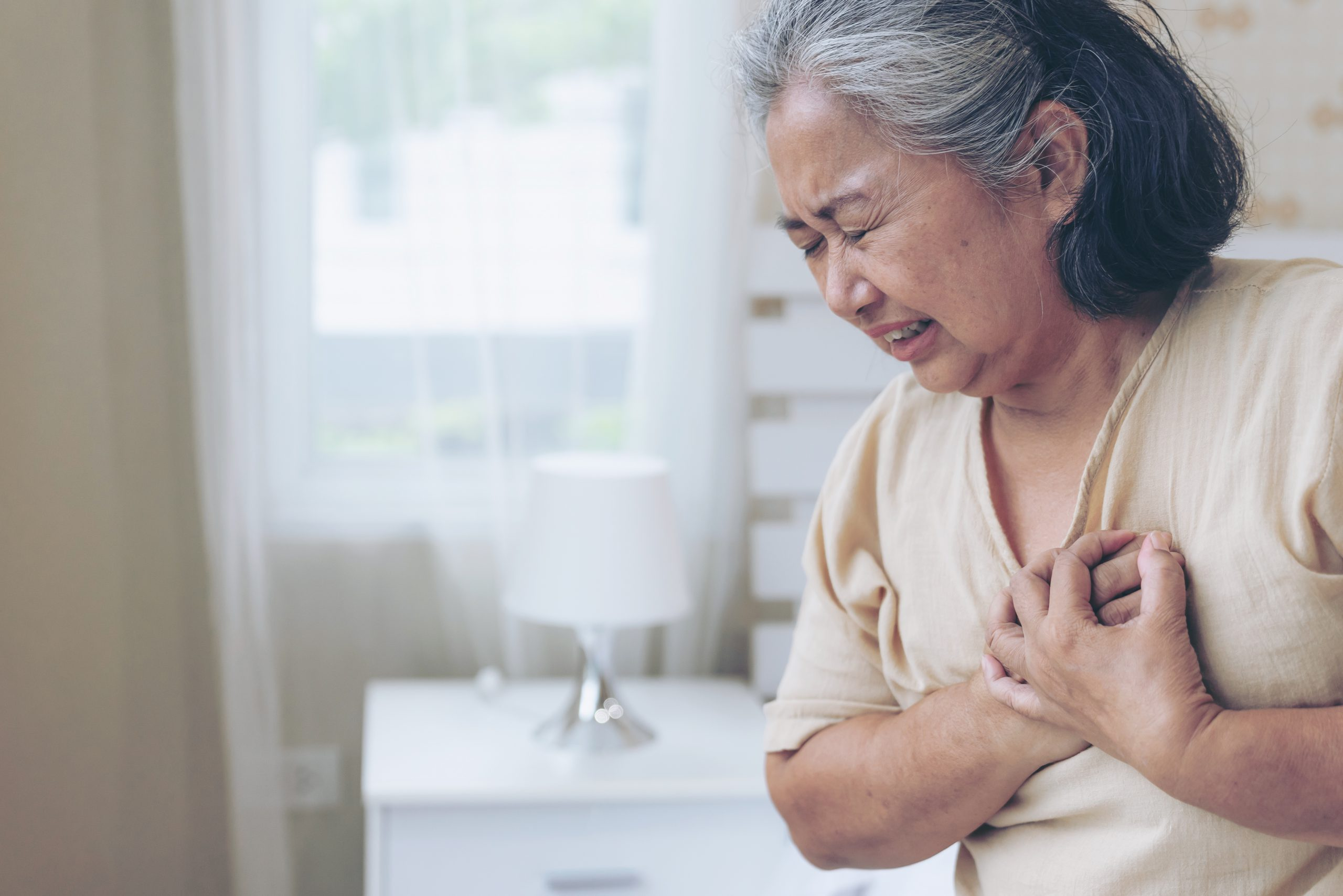 Asian woman clutching her chest from heart disease and CKD