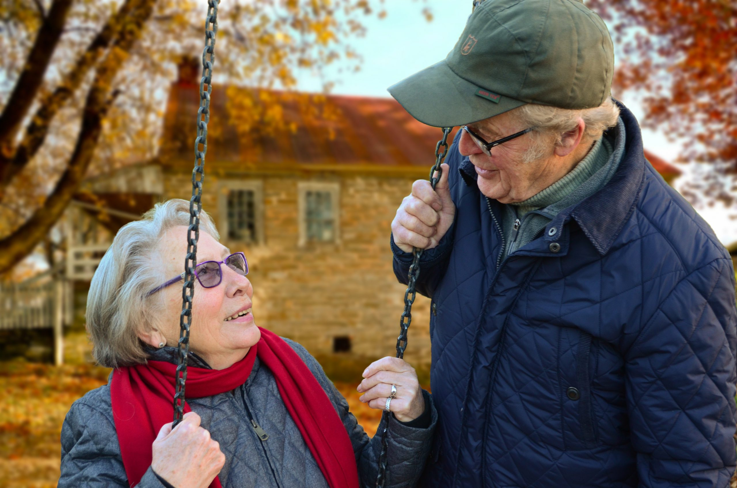 An elderly couple smile at one another outside while the woman sits on a swing