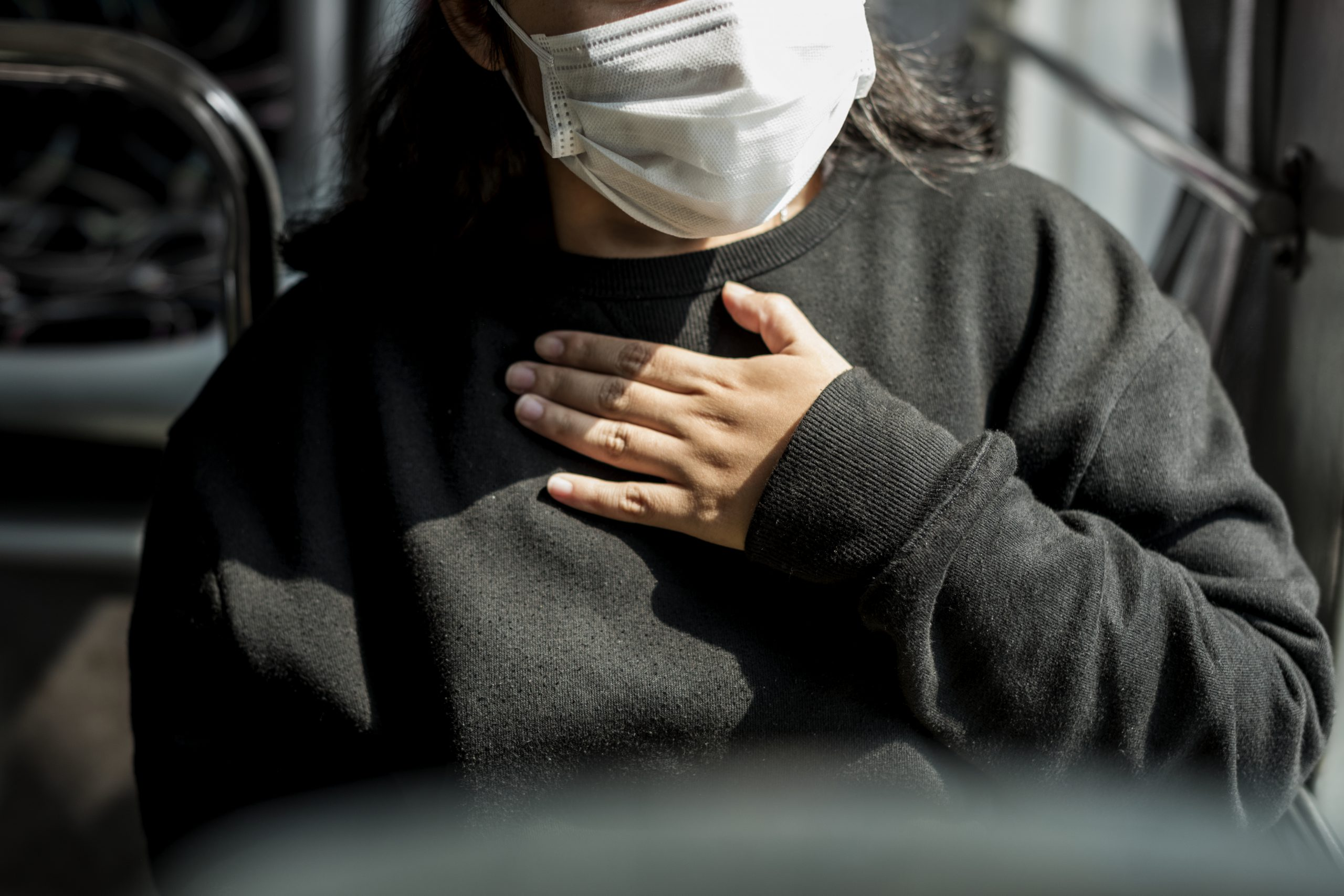 Woman wearing mask on bus with hand on chest trouble breathing long COVID